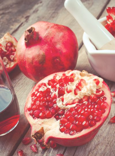 Pomegranate, juice in glass, mortar and pestle on wooden rustic table