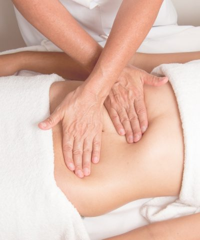woman receiving abdominal stomach massage treatment at spa