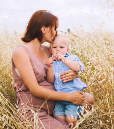 Beautiful pregnant woman and her cute toddler son having fun on wheat field with haystacks at summer day on nature, outdoors. Young mother waiting of a second baby. Pregnancy and family image. Mom and child
